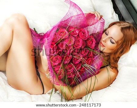 Romance. Beautiful young woman in bed with a big bouquet of red roses - stock photo
