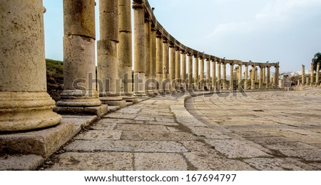 Romand and Ancient Greek typical columns in Rome City of Jerash in Jordan. Columns are offset on the lef side of photo - stock photo