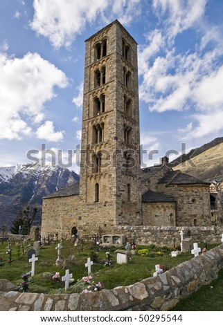 Romanesque church located in the Pyrenees, with a graveyard in the foreground and a snowy mountain in the background - stock photo