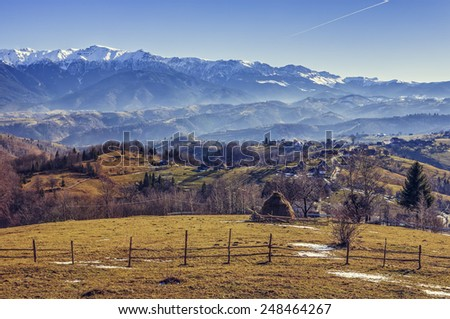 Romanian alpine rural scenery with sheepcote, haystack and remote village in the valleys of Bucegi mountains, Brasov county, Romania. - stock photo