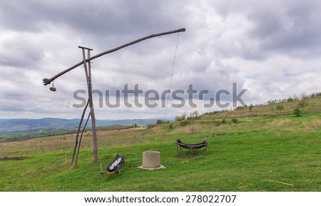 Romanian old wooden water well in the countryside used to give drink to thirsty farm animals - stock photo