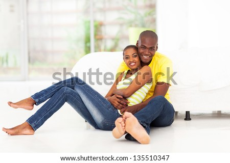 romantic african american couple sitting on bedroom floor - stock photo