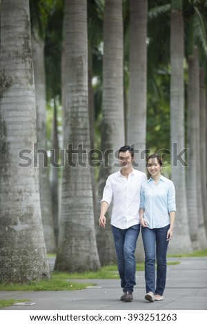 Romantic and happy Chinese couple walking down the street. Young Asian man and woman walking together. - stock photo