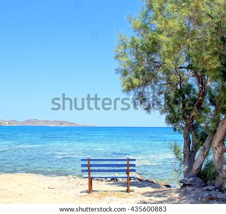 Romantic and iddyic resting place by the ocean; amazing view over the mediterranean sea with a little bench just at the right place for some shade under a tree.   - stock photo
