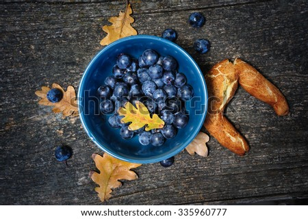 Romantic autumn still life with blackthorn berries in blue bowl and bagel on wooden board - stock photo