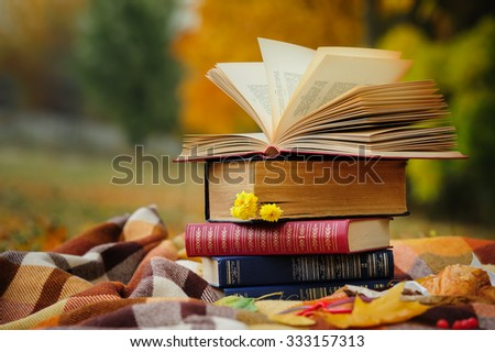 Romantic autumn still life with stacked books, plaid, croissant and leaves - stock photo