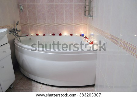Romantic bathroom with rose petals and candles - stock photo