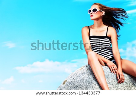 Romantic beautiful woman sunbathing on a seaside. - stock photo