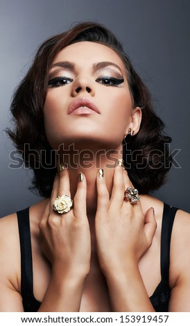 Romantic beauty. Vintage styled.Artistic make-up.Elegant black dress.Jewelry and fashion art.Looking up,hands covering the neck, close-up, head and shoulders, gray background, studio shoot. - stock photo