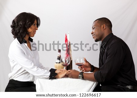 Romantic black couple sitting face to face at a table with a candle, a bottle of wine and two wine glasses for a dating view - stock photo