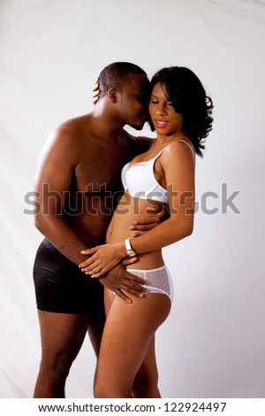 Romantic Black couple, standing and hugging and kissing each other tenderly - stock photo
