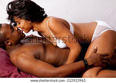 Romantic Black couple with him reclining and she sitting on his pelvis and kissing him - stock photo