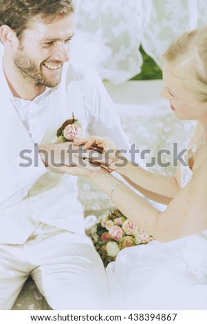 romantic boho wedding outside in green, the bride pushes her groom laughing the wedding ring on the finger. - stock photo