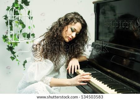 Romantic brunette girl playing piano, close up shot - stock photo