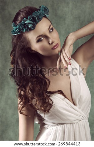 romantic brunette girl with long wavy hair posing in spring portrait with flowers on head and white dress - stock photo