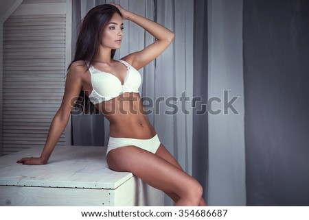 Romantic brunette young woman posing in white lingerie. Indoor photo. Ideal body. - stock photo