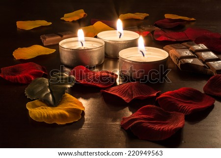 Romantic Candlelight With Chocolate and Rose Petals - stock photo