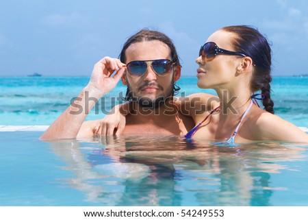 Romantic couple alone in infinity swimming pool - stock photo