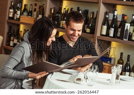 Romantic couple at a restaurant looking at the menu - stock photo
