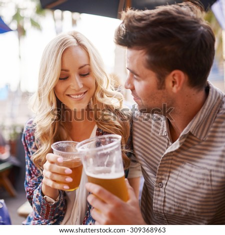 romantic couple drinking beer in outdoor pub or bar making a toast - stock photo