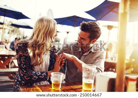romantic couple drinking beer with artistic lens flare - stock photo