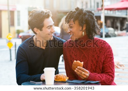 Romantic couple drinking coffee and eating croissants in a cafe. Young tourists enjoying breakfast in an outdoor cafe. Smiling couple in a happy conversation while eating brioches.  - stock photo