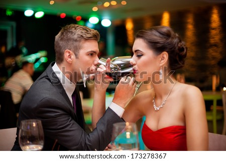 Romantic couple drinking wine with crossed arms  - stock photo