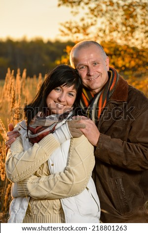Romantic couple embracing in autumn park backlit by sunset - stock photo