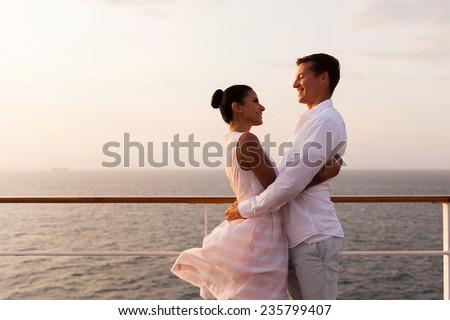 romantic couple embracing on cruise ship at sunset - stock photo