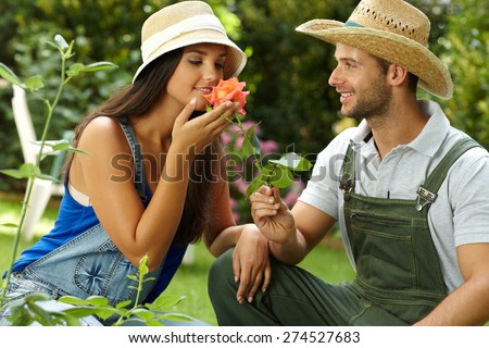 Romantic couple gardening, smelling rose at summertime, smiling. - stock photo