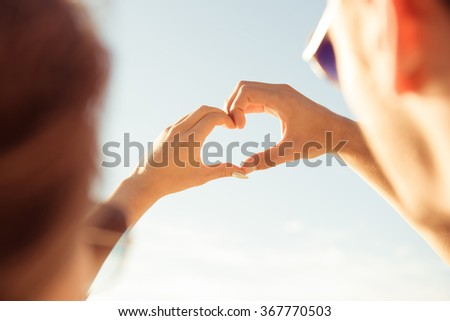 Romantic couple  gesturing a heart with fingers on a background of sky - stock photo