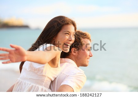 Romantic couple having fun on beach on honeymoon travel vacation summer holidays romance. Young happy lovers, Asian woman and Caucasian man doing playful joyful piggybacking ride outdoors. - stock photo
