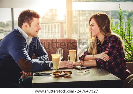 Romantic couple holding hands at coffee shop - stock photo