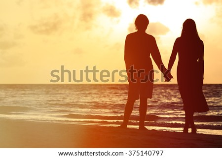 romantic couple holding hands at sunset - stock photo