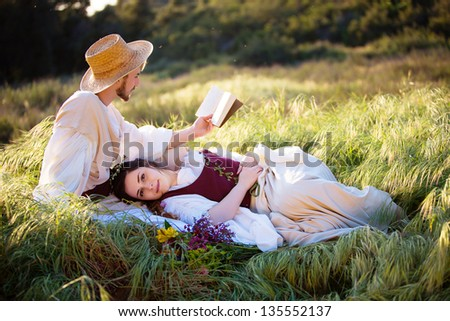Romantic couple in historical clothing relax and read in a country setting - stock photo