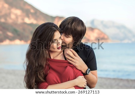 Romantic couple in love at beach sunset. Newlywed happy young lovers embracing enjoying honeymoon holiday.  - stock photo