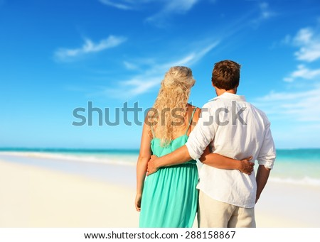 Romantic couple in love enjoying summer at beach. Young happy woman and man lovers embracing and hugging in romance on summer beach during honeymoon vacation holidays travel. - stock photo