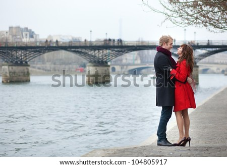 Romantic couple in love hugging near Pont des Arts in Paris - stock photo