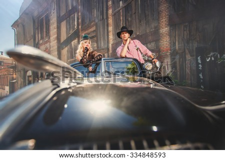 Romantic couple in love standing in retro-styled black car - stock photo