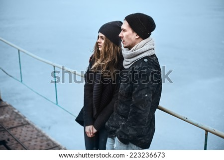 romantic couple in love young people on the docks in the winter - stock photo