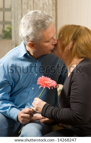 Romantic couple kissing on a couch, holding a bright flower. vertically framed shot. - stock photo