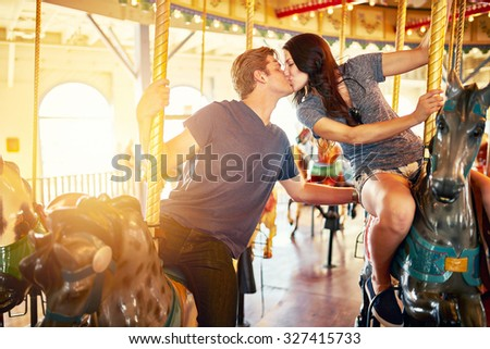 romantic couple kissing on merry go round shot with lens flare, selective focus, and blurred motion from action - stock photo