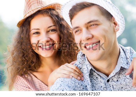 romantic couple lying on the grass in the summer park, spending time with loved ones - stock photo
