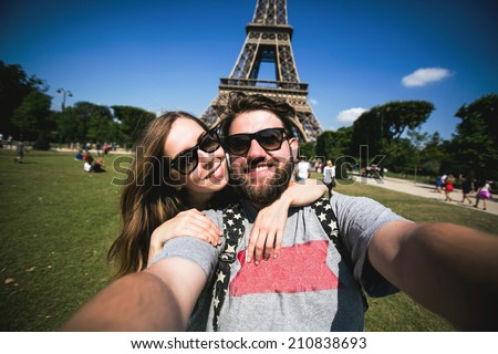 Romantic couple making selfie in front of Eiffel Tower while traveling in Paris, France. Happy smiling students enjoy their vacation in Europe. - stock photo