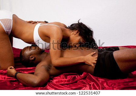 romantic couple of a man and woman, with the man laying on his back and his woman over him in sexual romantic position with touching and kissing - stock photo