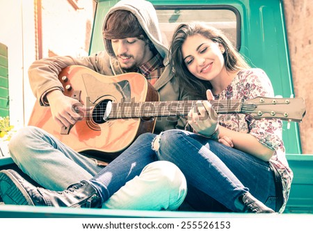 Romantic couple of lovers playing guitar on old fashioned mini car - Nostalgic retro concept of love with soft focus on the faces of boyfriend and girlfriend - Overexposed desaturated vintage filter - stock photo