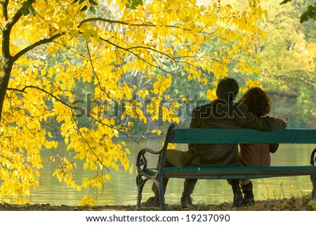 romantic couple on a bench by the lake in autumn - stock photo