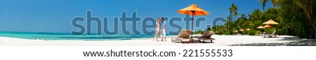 Romantic couple on a tropical beach during honeymoon vacation, super wide panorama perfect for banners - stock photo