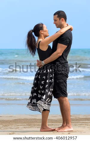 Romantic couple on beach.Young happy interracial couple looking to each other and smiling on beach. Asian woman,Caucasian man   - stock photo
