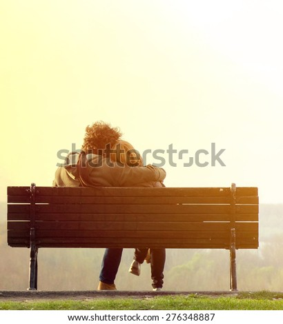 Romantic couple on bench - stock photo